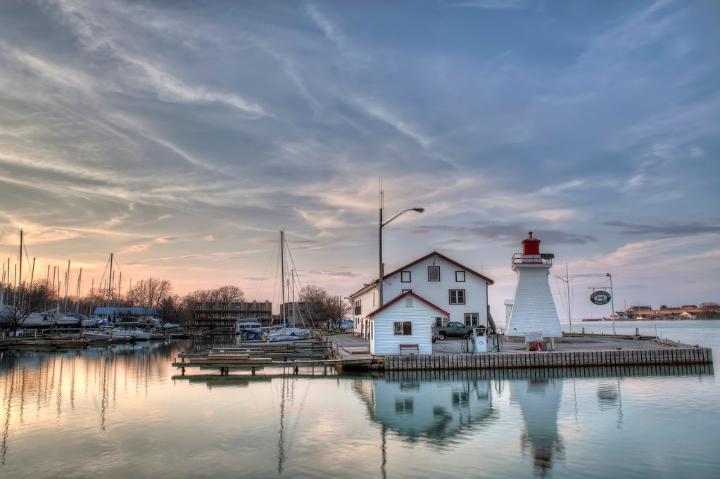 White boathouse and lighthouse showing reflections on calm water in marina on Lake Ontario in Niagara-on-the-Lake