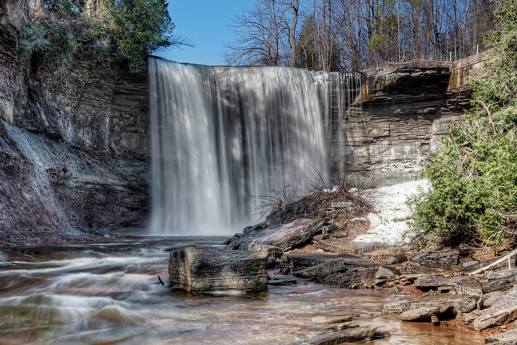 View of Indian Falls, Bruce County, Ontario from the bottom with the last of the snow melting besides the waterfall.