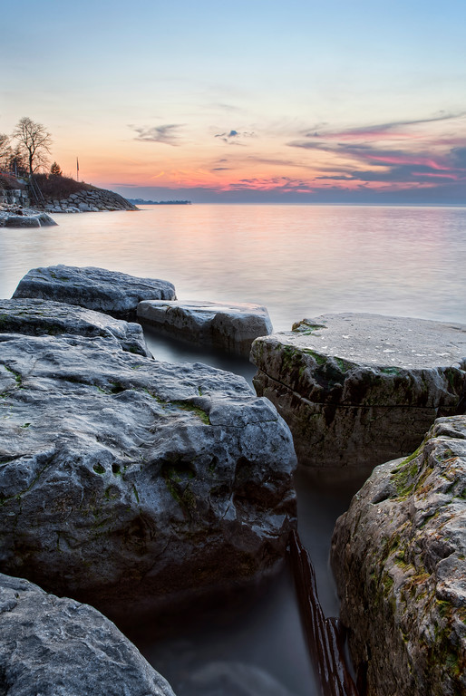 Large rocks at the edge of Lake Ontario's blue water with a sunset in the distance.