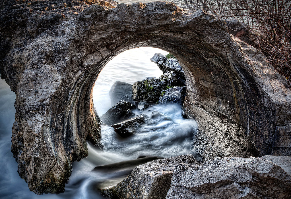 Round culvert through rocky hill with water rushing through and over rocks in Grey County, Canada.