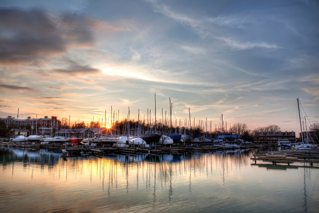 Sunset over a marina with sail boats on ground and masts reflecting at Niagara-on-the Lake in Ontario, Canada
