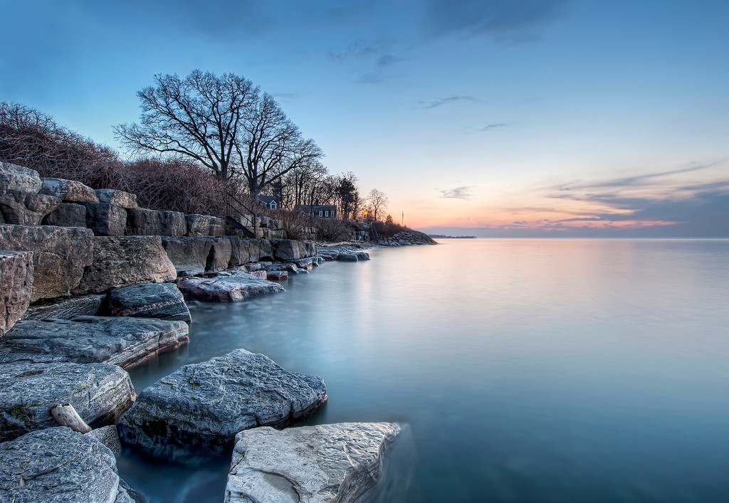 Last pink tinged light seen reflecting on calm Lake Ontario at Niagara-on-the-lake with rocky shoreline.