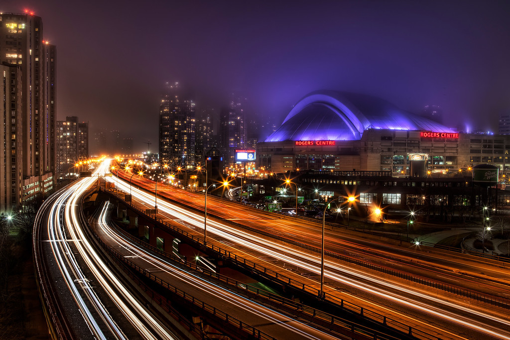 View of the Gardiner Expressway, Rogers Center and the CN Tower in Toronto from the top of the Queen's Quay Parking Garage with the purple lights of Rogers Center glowing in the fog and traffic flowing into the city.
