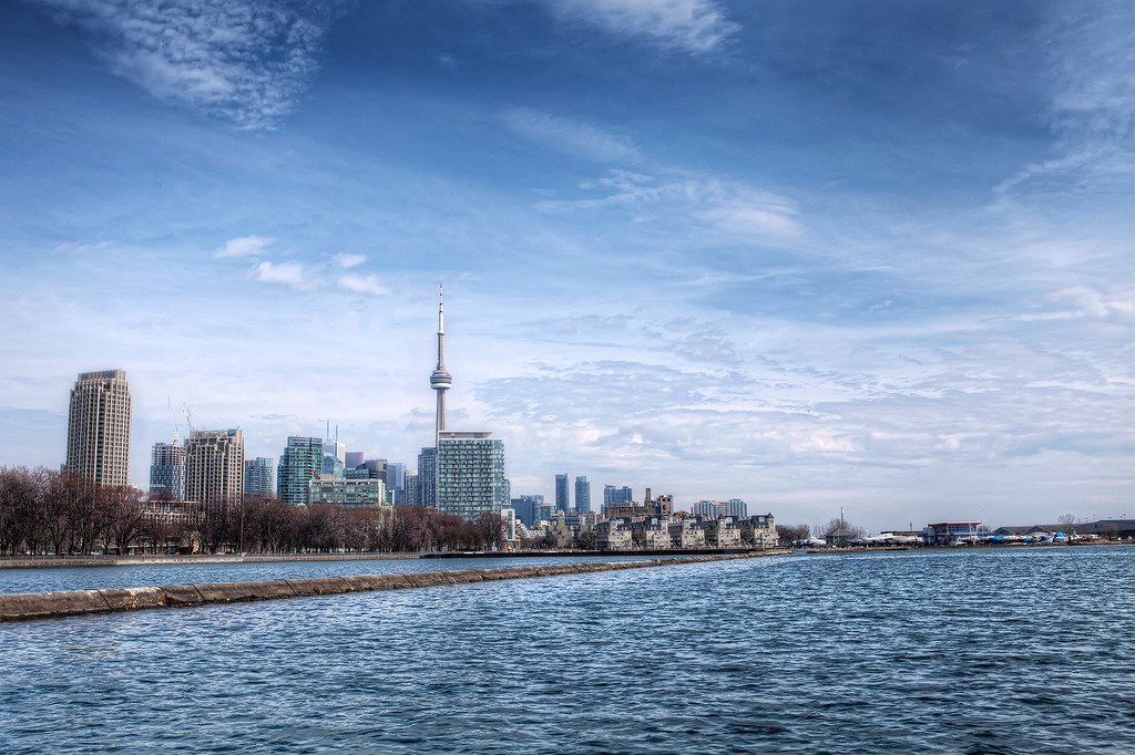 View of Toronto from the shoreline near Ontario Place under blue sky with fluffy clouds.