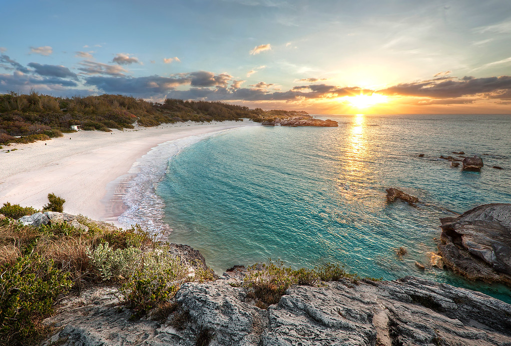 Horseshoe Bay Beach in Bermuda showing the cliff tops, pink sand, and golden sunrise reflecting on the turquoise water.