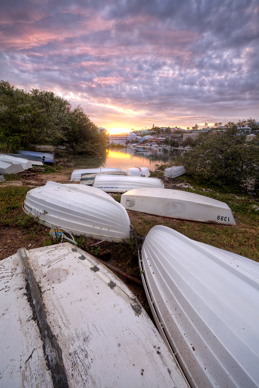 White dinghies upside down on the shore in front of a vibrant sunset sky at foot of the lane in Bermuda