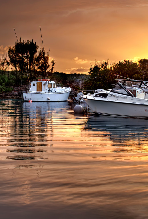 Little fishing boat anchored in its harbor in Bermuda at sunset.