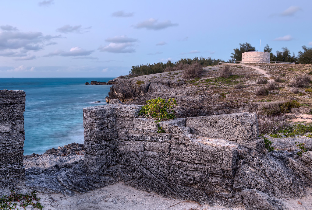 Martello Tower in Ferry Reach, Bermuda with aged limestone and turquoise ocean.
