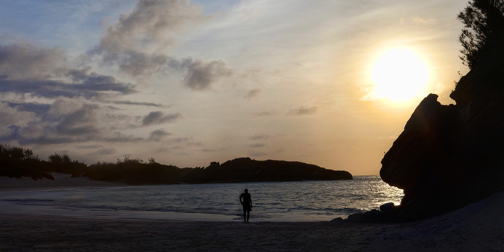 A man silhouetted against the morning sunrise as he enters the water at Horseshoe bay beach, Bermuda