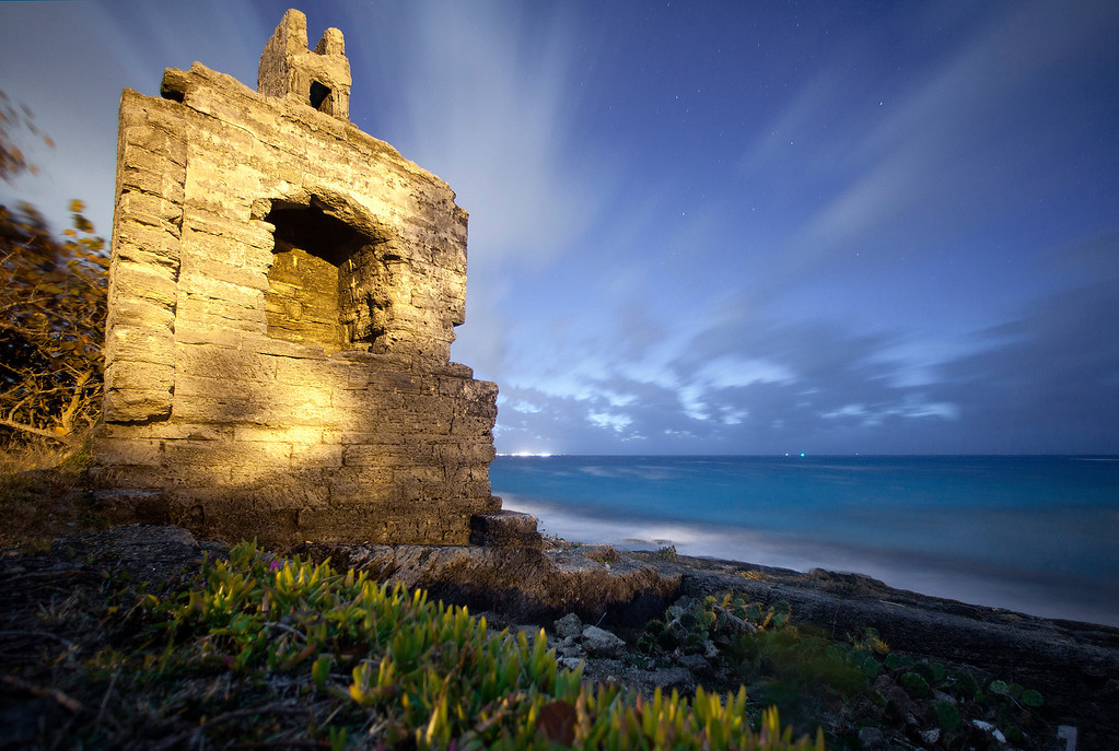 Remains of limestone chimney at ocean-side with turquoise waters and nighttime clouds and stars near Shelley Bay, Bermuda.