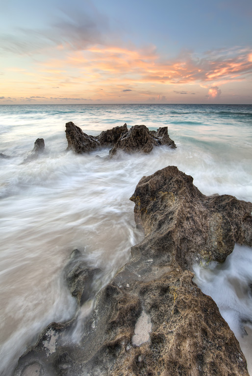 Sunrise view from Southlands, Bermuda with rocks jutting out from the foamy waves and turquoise ocean.