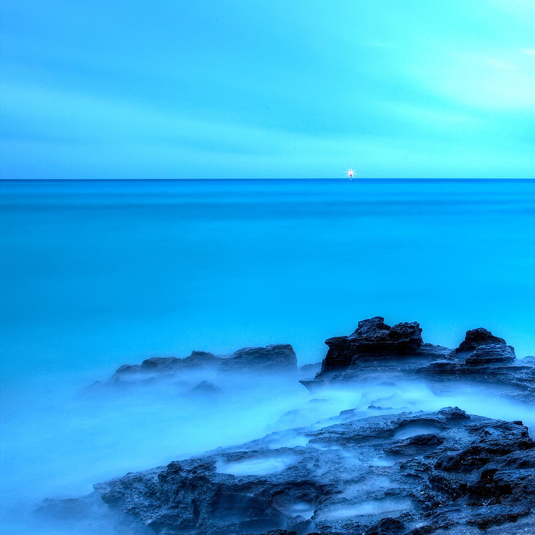 Calm turquoise blue ocean over the rocks with a channel marker alight on the horizon at Hog Bay Bermuda.