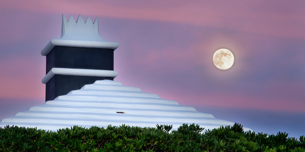 A pink and blue sky at sunset with a moonrise over a white Bermuda roof and chimney.