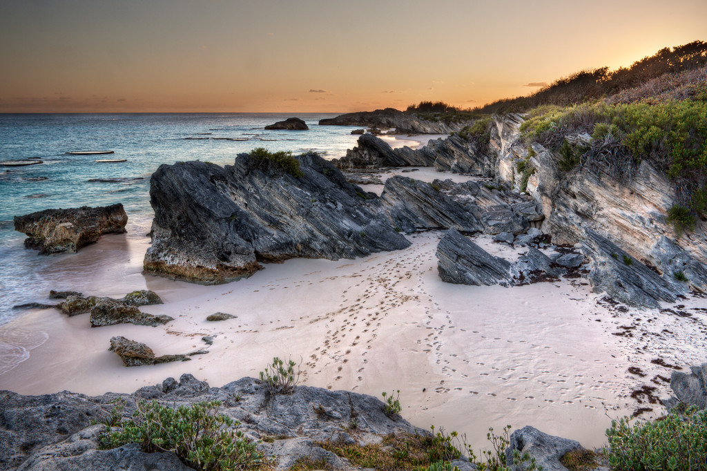 Footprints in the pink sand of a Bermuda cove beach between the rocks with turquoise ocean and orange sunset.