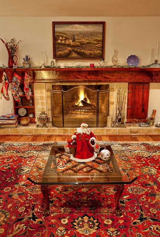 Christmas decorations including fat Santa on the coffee table in front of fireplace.