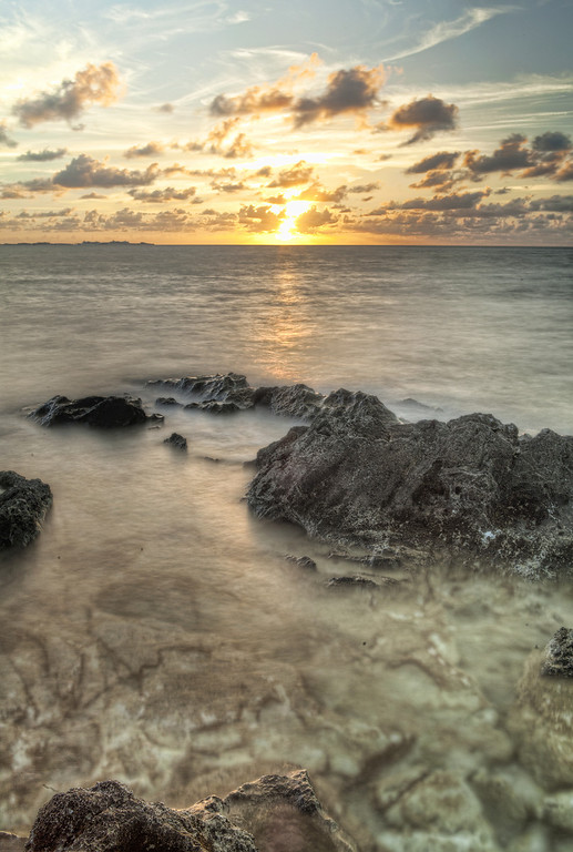 View of rocky reef ocean coast with golden sun setting on the horizon at the bottom of Crawl Hill in Bermuda.