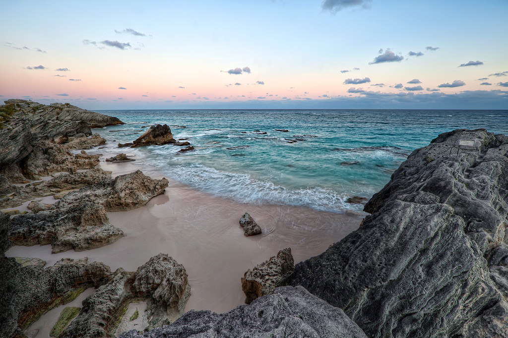 Rocky cove beach in Bermuda with pink sand and turquoise ocean with pink sunset sky.