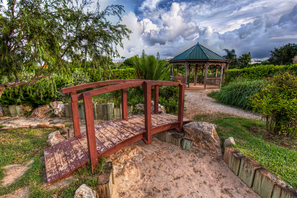 Japanese Zen Garden with wooden bridge in the Botanical Gardens in Bermuda with a gazebo and a dramatic sky with storm clouds
