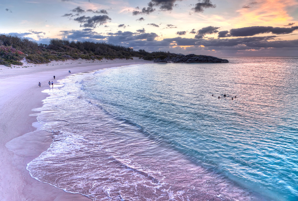 Sunrise at Horseshoe Beach, Bermuda with people exercising on pink sand and swimming in turquoise ocean.