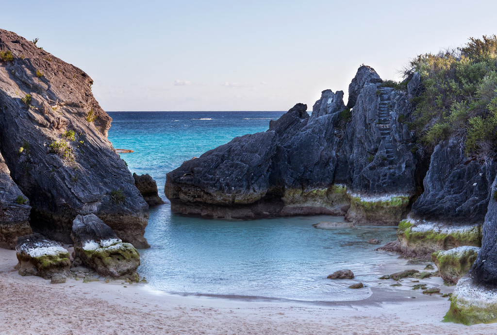 Stone Hole Bay, Bermuda, a cove beach with turquoise ocean and a set of stairs carved into the cliff.