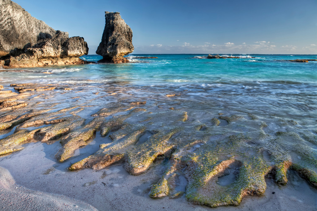 Early evening winter shot at Chaplain Bay, Bermuda when the rocks on the beach are uncovered and turquoise ocean.
