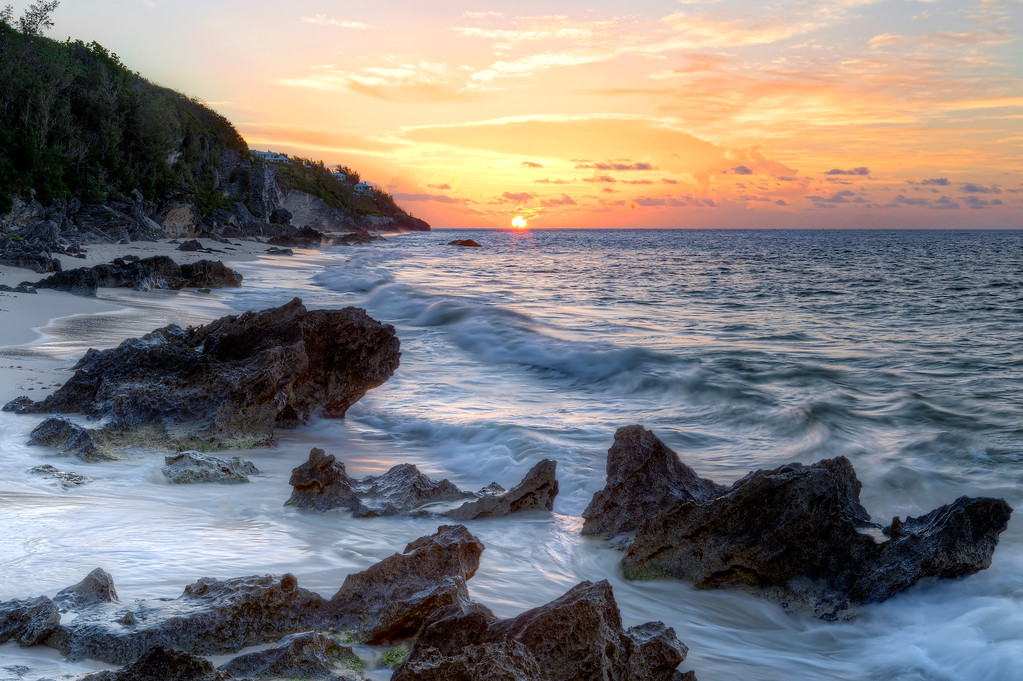 Orange and purple sunrise just peaking over the ocean on the horizon with waves breaking over the rocks on Southlands beach Bermuda