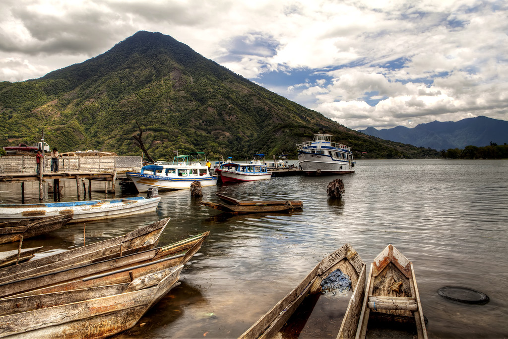 canoes on the shore of lake atitlan Guatemala with a volcano and blue sky in the background