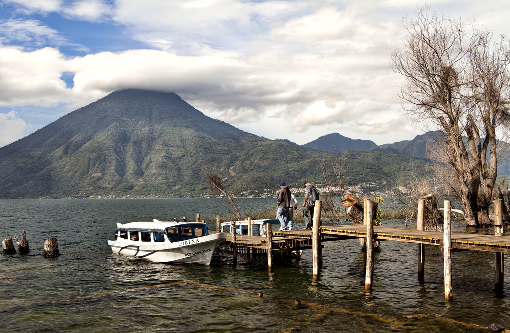 cloud capped volcano and ferry stop with ferry on lake atitlan guatemala