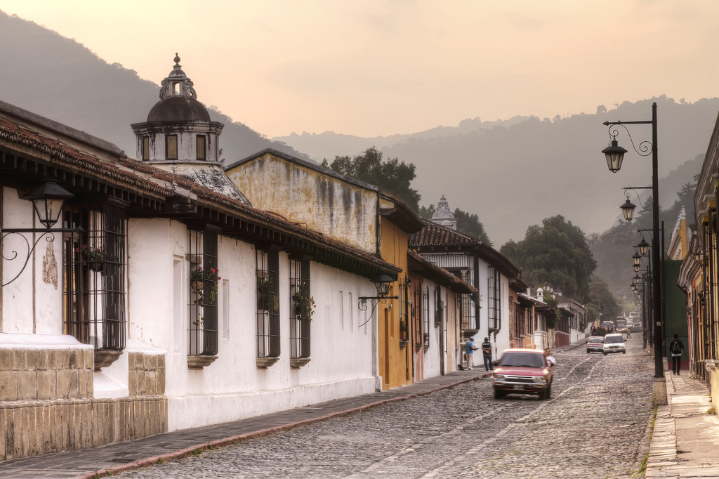 Old colonial style, straight street in Antigua, Guatemala with old cars with forest in the background.