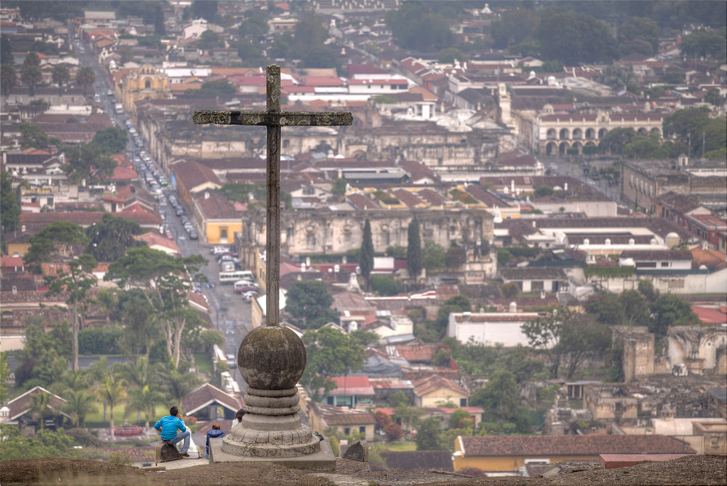the cross above antigua guatemala with the city in the background