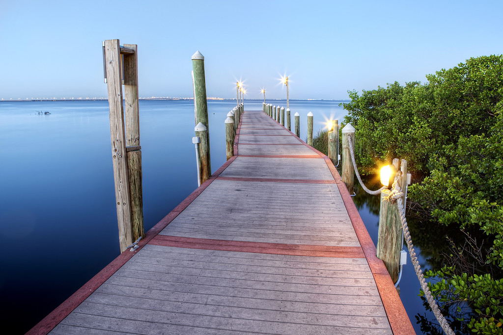 Long wooden boat dock with lights on calm blue sea during the blue hour at the Hyatt Resort in Tampa Bay, Florida
