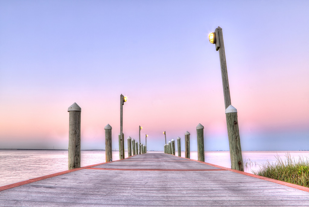 A boat dock extends to the horizon at sunrise, in front of a pink sky at the Hyatt Resort in Tampa, Florida.