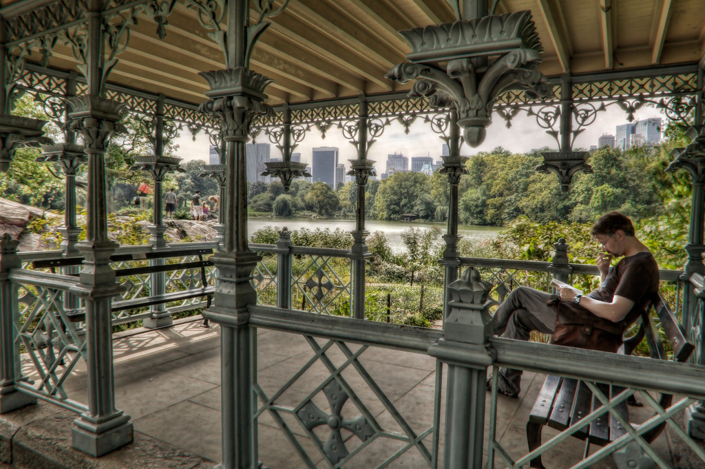 A man reading inside a detailed cast iron gazebo in Central Park, New York showing the lake and skyline in the distance.