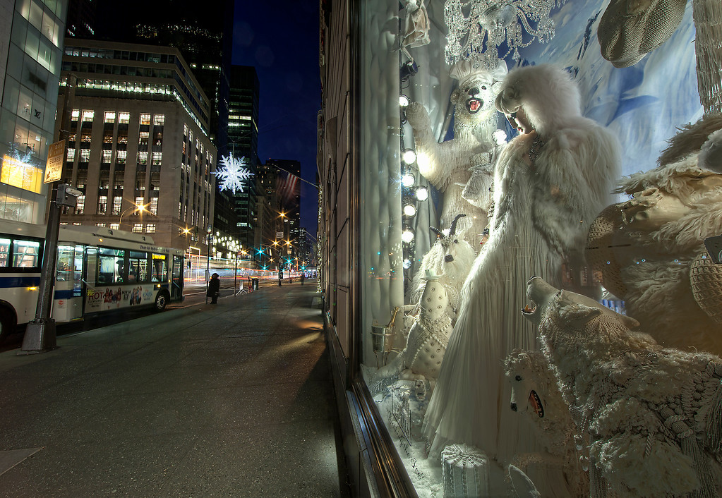 Bergdorf Goodman's 2011 white Christmas window with lady, attacking bear and other animals while showing 5th avenue in the downtown direction.