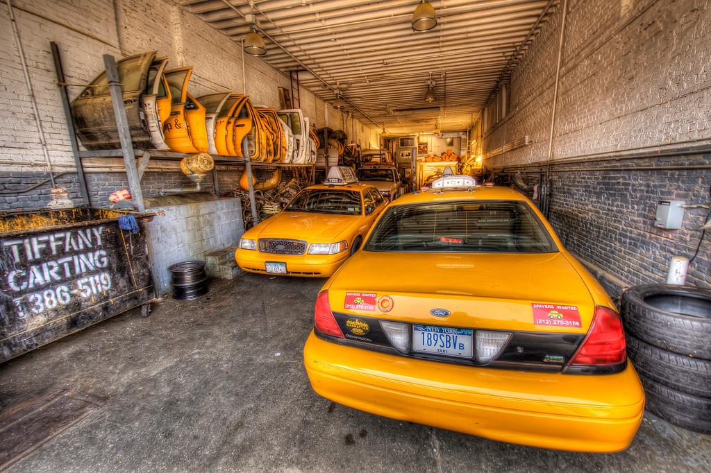 Long skinny yellow taxi garage with a row of spare doors on the wall in New York City.