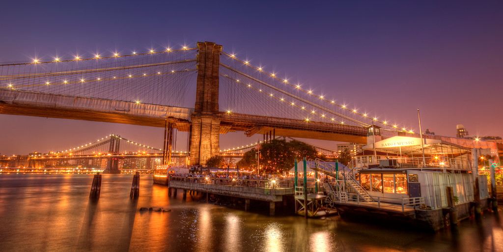 Party barge under the Brooklyn Bridge with golden lights reflecting on the river and bridges under a purple night sky in New York City.