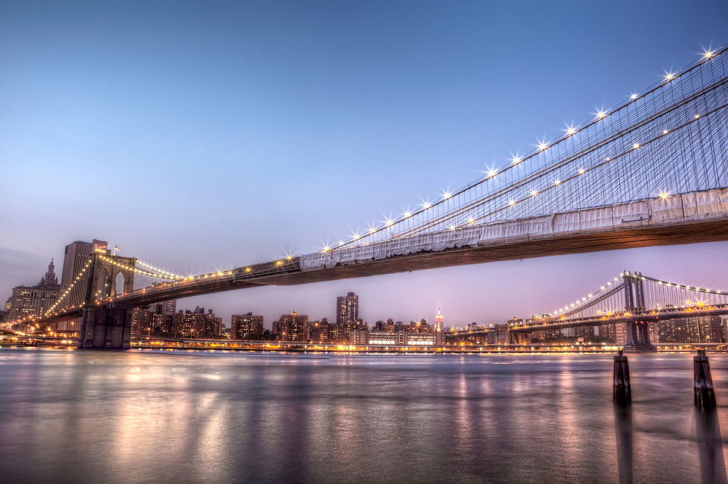 View of New York City with the Empire State Building from under the Brooklyn Bridge after sunset