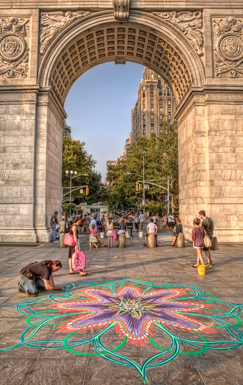 Sand painter, Joe Mangrum, creates a fantastic work in Washington Square Park in New York City in front of the arch while a baby grand piano is being played by Colin Huggins under the arch with people watching.