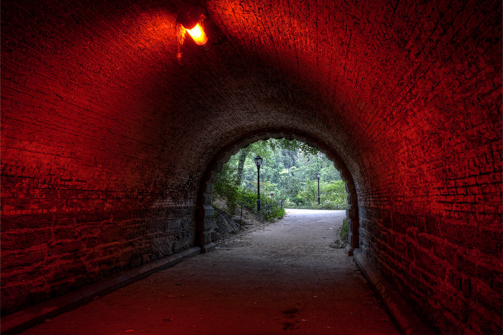 Brick tunnel bathed in red light looking out at a green bordered path in Central Park, New York City.