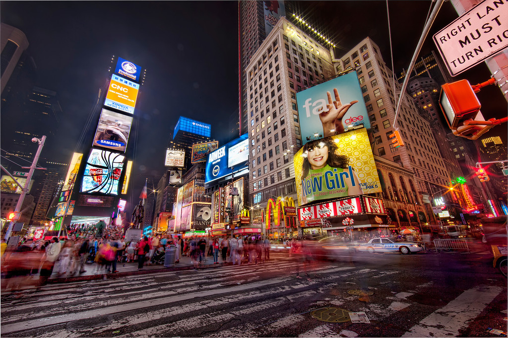 Times Square, New York City at night showing a rush of people and traffic, neon billboards, and the street markings.