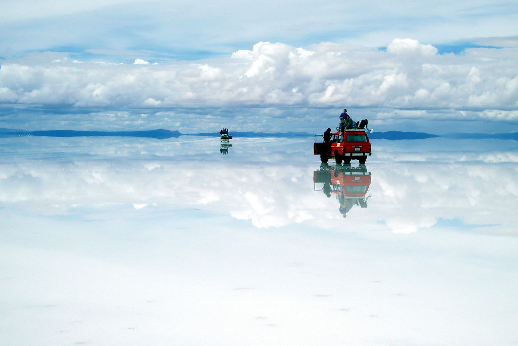 Two red jeeps reflected with the sky and clouds on the Ayuni Desert Salt flats