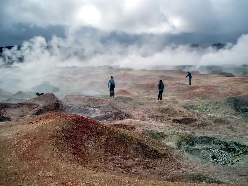 people walking though steaming red thermal mud vents in ayuni bolivia