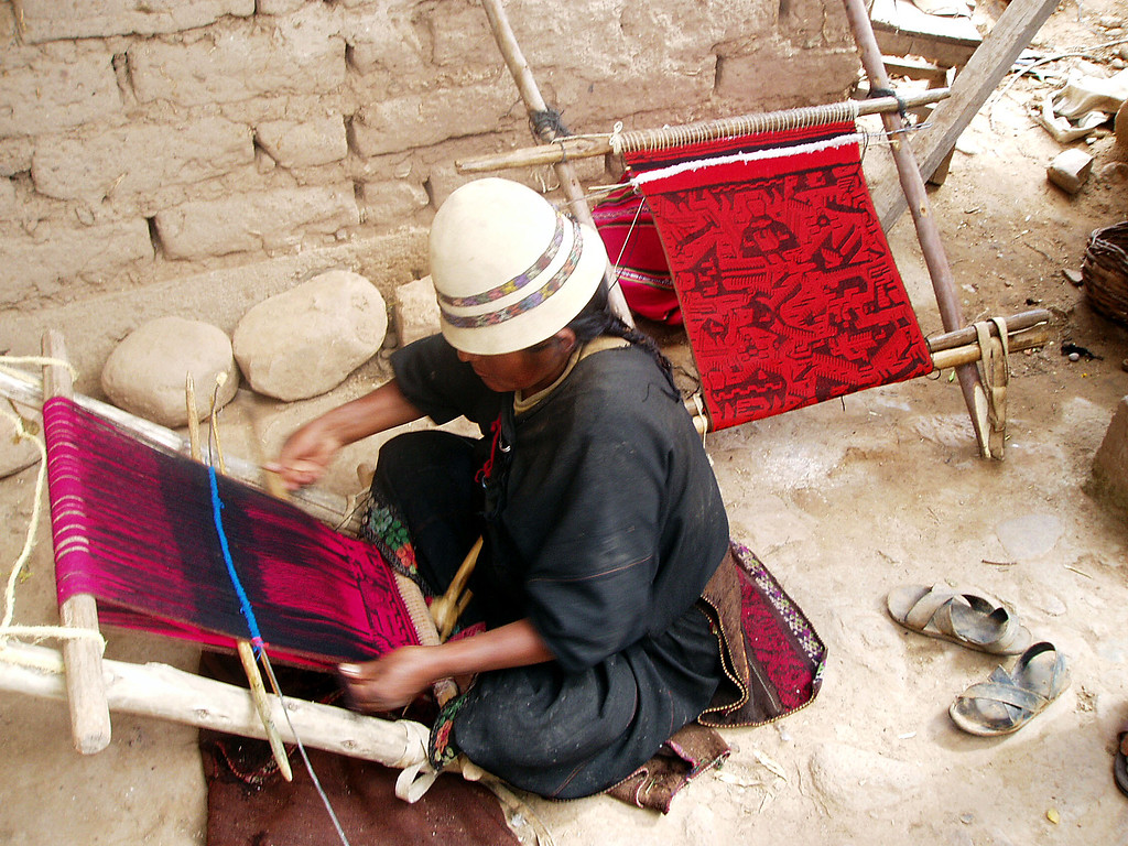 quechuan lady weaving on a loom kneeling with sandals off and compeleted work on another loom next to her