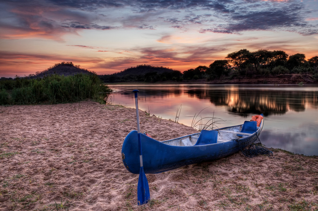Blue canoe and paddle on the shore of the Lower Zambezi River, Zambia at sunrise with the trees and orange sky reflecting in the river.