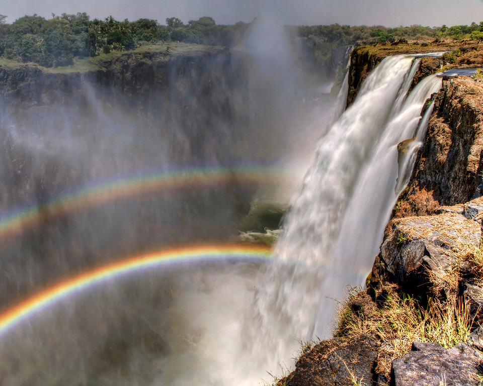 Victoria Falls at low water in route to Devils Hole with a double rainbow in Zambia
