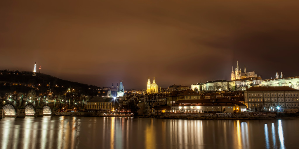 Nighttime view of Prague skyline including St. Vitus Cathedral, Church of St. Nicholas, gateway to Charles Bridge leading into the bridge with lights reflecting on river.