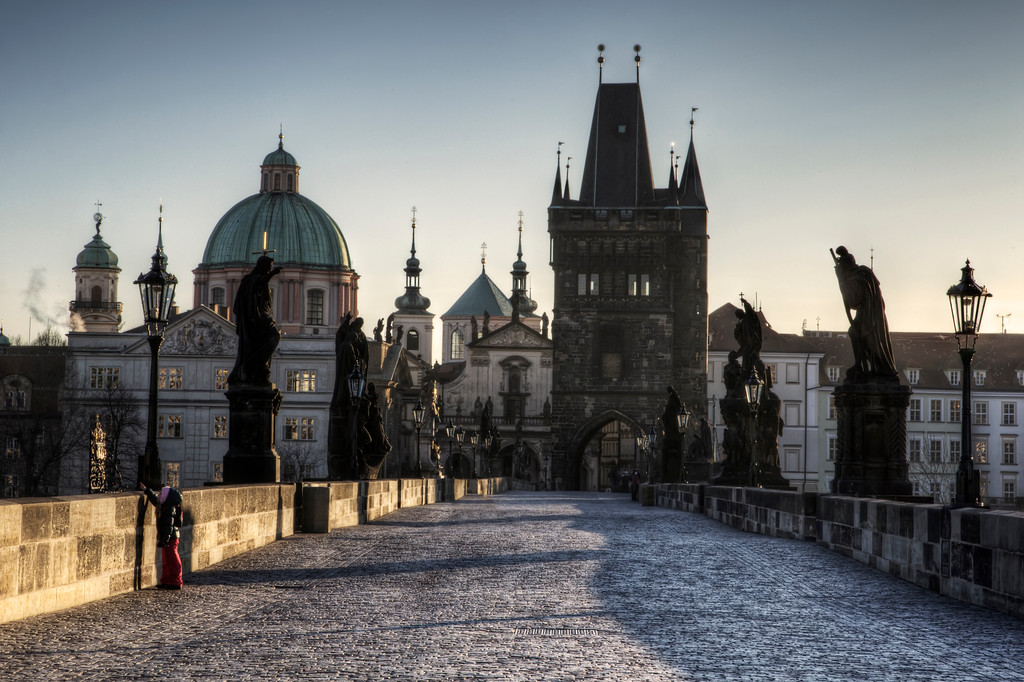 Charles Bridge with statues and little girl and view of Old Town, Prague.
