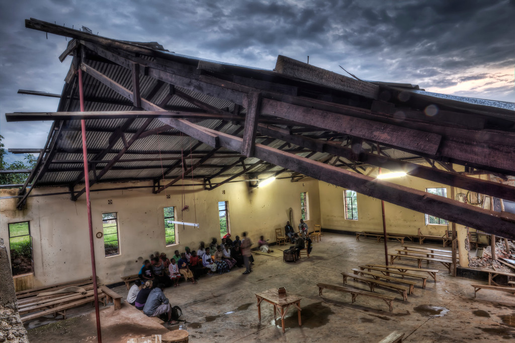 Interior of church in Gisenyi, Rwanda with an unfinished roof open to the stormy sky and the local choir practicing.