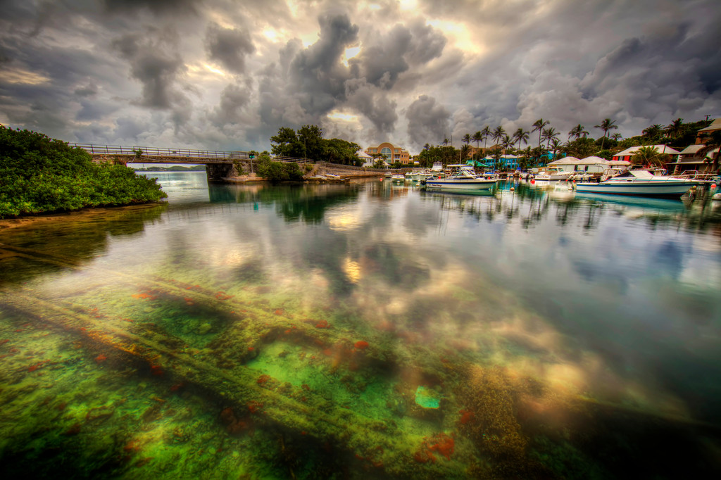 Flatts Inlet, Bermuda with boats, bridge, green and orange coral under the water with dramatic clouds.