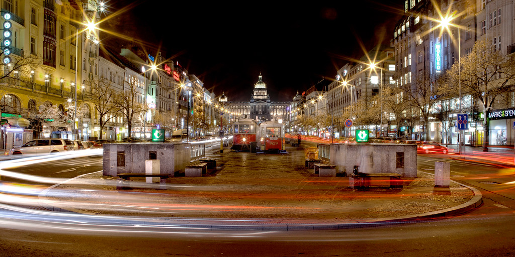 Wenceslas Square in Prague lit up at night with light trails from traffic rounding the bend.